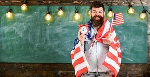 Den amerikanska läraren med amerikanska flaggan rymmer ringklockan Amerikanskt utbildningssystembegrepp Man med skägget på lyckli Fotografering för Bildbyråer