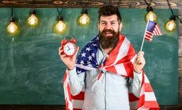 Den amerikanska läraren med amerikanska flaggan rymmer ringklockan Man med skägget på gladlynt framsidahållflagga av USA och kloc Royaltyfri Fotografi
