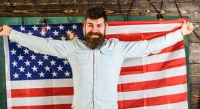 Den amerikanska läraren rymmer amerikanska flaggan Man med skägget och mustasch på lycklig framsidahållflagga av USA, träbakgrund Fotografering för Bildbyråer