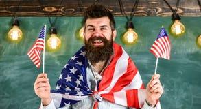 Den amerikanska läraren vinkar med amerikanska flaggan Mannen med skägget och mustaschen på lycklig framsida rymmer flaggor av US Royaltyfria Bilder