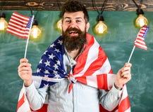 Den amerikanska läraren vinkar med amerikanska flaggan Mannen med skägget och mustaschen på lycklig framsida rymmer flaggor av US Fotografering för Bildbyråer
