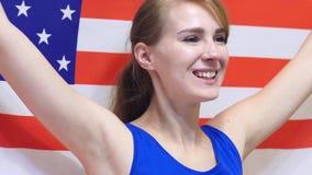 Den amerikanska unga kvinnan firar rymma flaggan av USA i ultrarapid arkivbilder