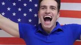 Den amerikanska unga mannen firar rymma flaggan av USA i ultrarapid arkivfoto