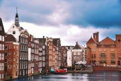 Den Amsterdam kanalen Singel med typiska holländarehus och husbåtar under morgon slösar timmen, Holland, Nederländerna Använd ton Arkivbild