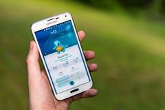 Den Android användaren som spelar Pokemon, går Arkivfoton