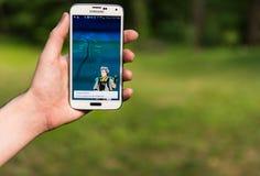 Den Android användaren som spelar Pokemon, går Arkivbilder