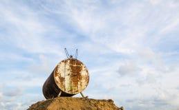 Den anfrätta och rostiga trumman för olje- lagring mot härliga blått skidar Royaltyfri Fotografi