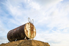 Den anfrätta och rostiga trumman för olje- lagring mot härliga blått skidar Royaltyfria Bilder