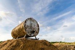 Den anfrätta och rostiga trumman för olje- lagring mot härliga blått skidar Royaltyfria Foton