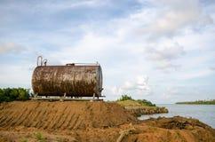 Den anfrätta och rostiga trumman för olje- lagring mot härliga blått skidar Royaltyfri Bild