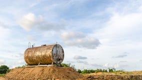 Den anfrätta och rostiga trumman för olje- lagring mot härliga blått skidar Arkivfoto