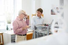 Den angenäma allmäntjänstgörande läkaren som talar med hans arbetsledare, medan skriva ut 3D, modellerar Royaltyfri Foto
