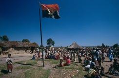 Den angolanska nationella flaggan i ett läger, Angola. Arkivfoton