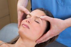 Vänder mot den avslappnande theraphyen för ansikts- massage på kvinna royaltyfria foton