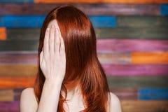 Den ansiktslösa flickan täcker hennes framsida med hans hand Arkivfoton