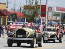Den antika bilen med amerikanska flaggan ståtar in i lilla staden Amerika Royaltyfria Bilder