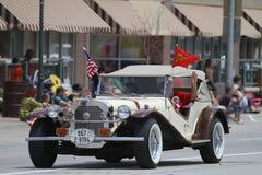 Den antika bilen med taket med amerikanska flaggan ståtar in i lilla staden Amerika Royaltyfri Fotografi