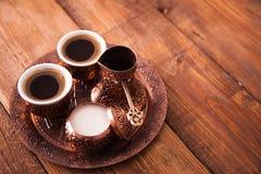 Den antika bronskannan och kaffekoppen ställde in med data i ett magasin I royaltyfri foto