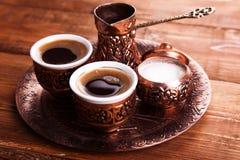 Den antika bronskannan och kaffekoppen ställde in med data i ett magasin I arkivbilder