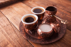 Den antika bronskannan och kaffekoppen ställde in med data i ett magasin I royaltyfri bild
