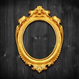 Den antika guld- ramen på träväggen; Tom antik guld- pictu Fotografering för Bildbyråer