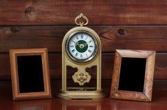 den antika klockan inramniner det gammala fotoet Arkivfoton