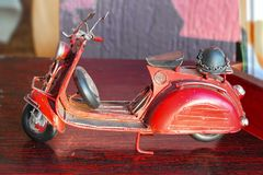 Den antika miniatyrröda leksaken diecast trehjulingsparkcykeln med den tyska hjälmen på baksida royaltyfri bild