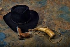 Den antika pistolen och pulverhornet med cowboyhatten kritiserar på Arkivbilder