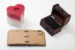 Den antika retro dagboken och stearinljuset i hjärta formar Arkivbilder