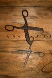 Den antika retro objektmonteringen för gammal stil på en trävägg scissors Bakgrund royaltyfri bild