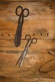 Den antika retro objektmonteringen för gammal stil på en trävägg scissors Bakgrund royaltyfria foton