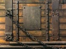 Den antika trädörren med metallplattan spikar och kedjan royaltyfria bilder