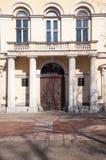 Den antika ytterdörren med antika poler Arkivfoto