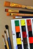 Den använda vattenfärgen målar och många borstar, den lekmanna- lägenheten, bästa sikt Fotografering för Bildbyråer