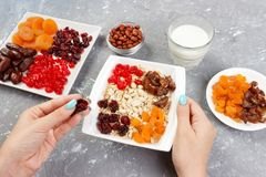 Den användbara och sunda frukosten flickan förbereder hennes mysli för frukost som den torkade flickan sätter sig - bära frukt i  Arkivbild