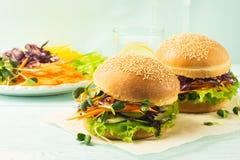 Den aptitretande hamburgaren gjorde från nya grönsaker och gräsplaner på en blå bakgrund Begrepp av vegetarisk sund mat arkivfoton