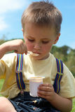 den aptitretande pojken äter little yoghurt royaltyfria bilder