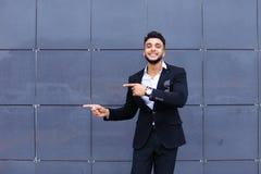 Den arabiska grabben i affärsmitt står le att gå som är långsamt royaltyfria foton