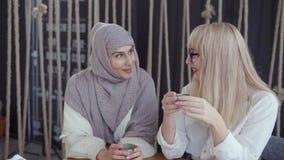 Den arabiska kvinnan är samtal som är hemligt till hennes blonda kvinnliga vän under att dricka te stock video