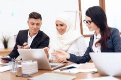 Den arabiska kvinnan i hijab arbetar i kontoret samman med hennes kollegor royaltyfri foto