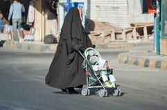 Den arabiska kvinnan i hijab för vagnen med barnet Arkivbild