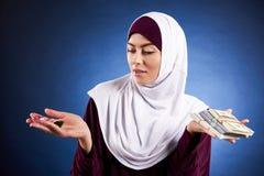 Den arabiska kvinnan i hijab rymmer packen av dollar arkivbilder