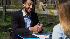 Den arabiska mannen och den Caucasian kvinnan har affärsmöte i kafé lager videofilmer