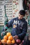 Den arabiska mannen säljer granatäpplefruktsaft på Jerusalem den gamla stadsmarknaden Royaltyfri Bild