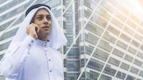 Den arabiska mannen står och använder mobiltelefonen på utomhus- stadsutrymme på M royaltyfria foton