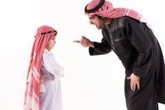 Den arabiska missbelåtna fadern grälar på sonen i person som tillhör en etnisk minoritet royaltyfri fotografi