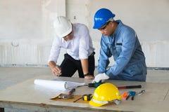 Den arbetsledareordföranden eller arkitekten diskuterar med den tekniska teknikern Royaltyfri Bild