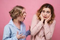 Den arga unga kvinnan skriker på hennes vän i ursinne Offret av agression och psykologiskt våld i skräck stänger henne öron fotografering för bildbyråer