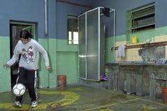 Den argentinska pojken är hemmastadd med bollen som spelar fotboll Royaltyfri Bild