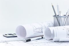 Den arkitektoniska ritningen rullar och plan, teknik och kontoret arkivbilder